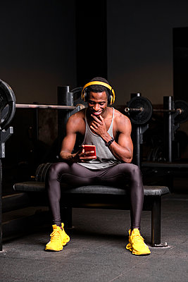 Smiling young African man with headphones using smart phone at gym - p300m2273621 by Antonio Ovejero Diaz