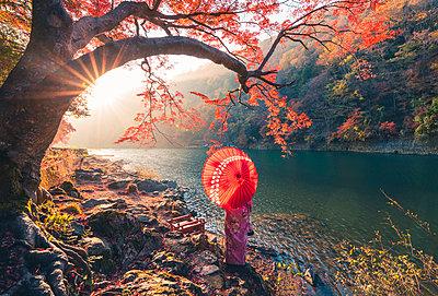 Arashiyama, Kyoto, Kyoto prefecture, Kansai region, Japan. Woman with red umbrella and kimono admiring the view on Katsura river (MR). - p651m2062124 by Marco Bottigelli