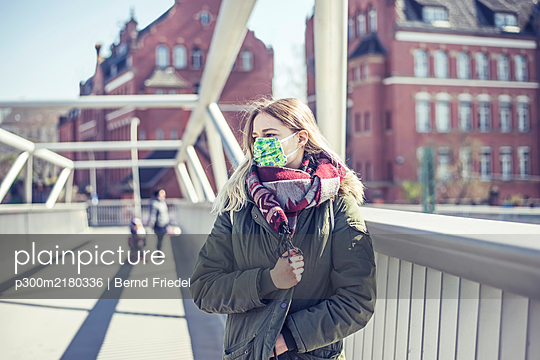 Portrait of young woman wearing mask on a bridge in the city - p300m2180336 by Bernd Friedel