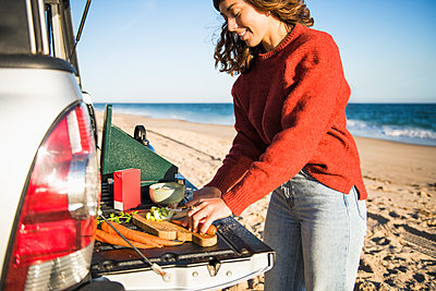 Young woman tailgating cooking while beach car camping alone - p1166m2285570 by Cavan Images