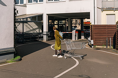 Woman pushing shopping cart outside supermarket - p300m2171184 by Mareen Fischinger