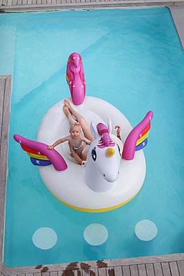 Mother and son in inflatable in pool - p924m2074241 by Bean Creative