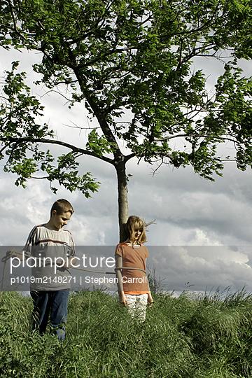 Boy tying girl to tree - p1019m2148271 by Stephen Carroll