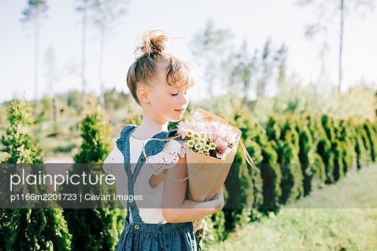 portrait of a pretty young girl holding a beautiful bouquet of flowers - p1166m2201723 by Cavan Images