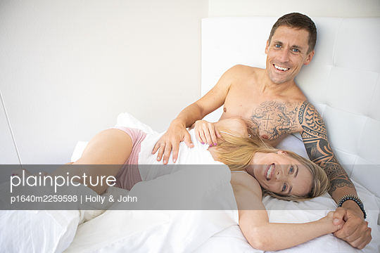 Couple in love embracing in bed - p1640m2259598 by Holly & John