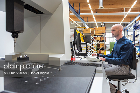 Man using computer at machine in modern factory - p300m1581658 von Daniel Ingold