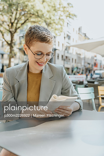 Smiling woman reading book sitting in sidewalk cafe on sunny day - p300m2226922 by Mareen Fischinger