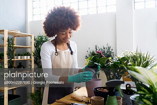 Afro woman gardening in a plant laboratory or shop, small business owner - p300m2287690 von Giorgio Fochesato