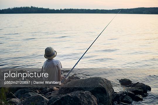 Boy fishing in lake - p352m2120897 by Daniel Wahlberg