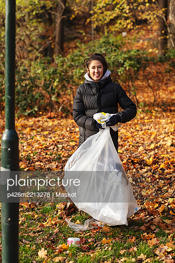 Portrait of smiling female environmentalist with plastic waste standing in park during autumn - p426m2213278 by Maskot