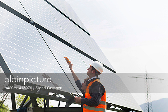 Male and female engineers using multimeter on solar panels - p429m1418076 by Sigrid Gombert