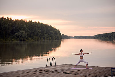 Woman practicing warrior 2 pose on pier by lake against cloudy sky during sunset - p1166m2011226 by Cavan Images