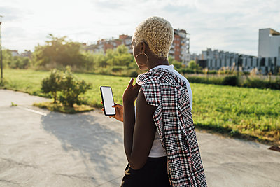 Young black diverse woman doing videocall outdoor using smartphone - Milan, Lombardy, Italy - communication, conversation, new normal concept - p300m2294068 von Eugenio Marongiu
