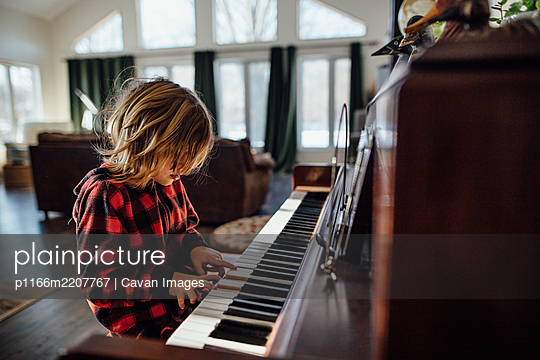 Little boy with messy hair playing the piano - p1166m2207767 by Cavan Images