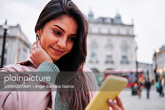 Smiling woman looking at mobile phone in city - p300m2273681 by Angel Santana Garcia