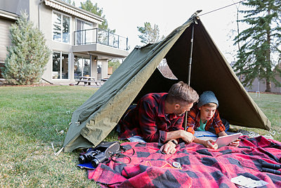 Father and son using digital tablet in backyard tent - p1192m1145609 by Hero Images