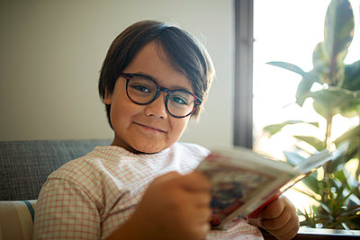 Portrait of smiling boy with glasses reading book at home - p300m2167582 by Valentina Barreto