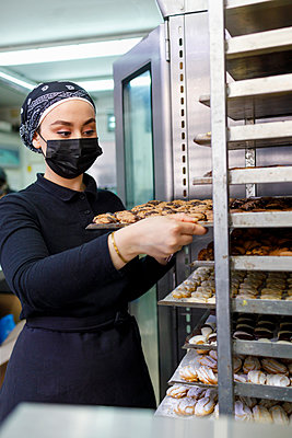 Female entrepreneur putting tray in rack at bakery - p300m2281901 by Ignacio Ferrándiz Roig