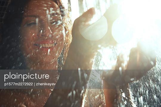 Woman taking a shower, portrait - p1577m2272922 by zhenikeyev