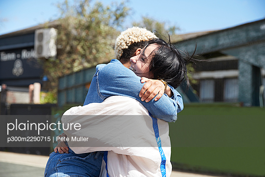 Happy lesbian couple hugging on sunny day - p300m2290715 by Pete Muller