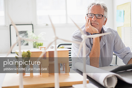 Older Caucasian architect examining scale model in office