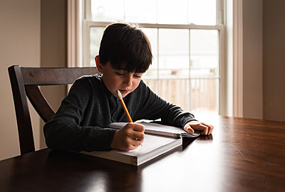 Young boy doing schoolwork in a workbook at home at the table. - p1166m2174191 by Cavan Images