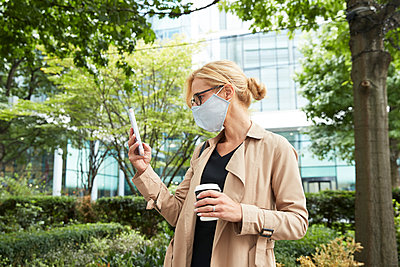 Woman holding coffee cup while using mobile phone in city - p300m2227061 by Pete Muller