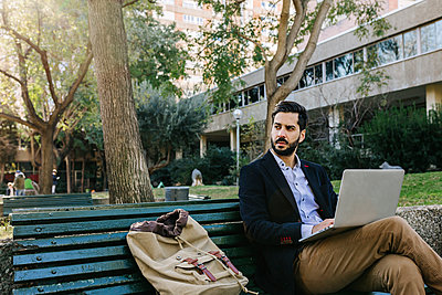 Confident businessman with laptop looking away while sitting on bench - p300m2257509 by Xavier Lorenzo