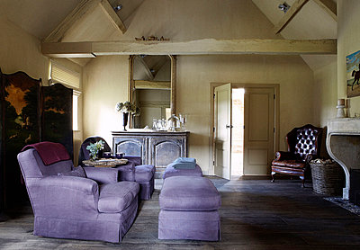 Lilac coloured armchairs with foot rests and folding screen in living room of country home - p349m790178 by Brent Darby