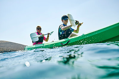 Teenage boy and mother sea kayaking, surface level side view, Limnos, Khios, Greece - p924m2097717 by Ross Woodhall