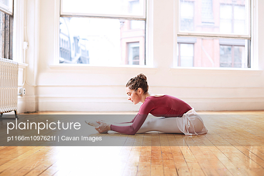 Young ballet dancer stretching in studio
