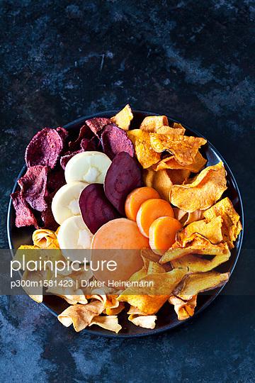 Sliced root vegetables and vegetable chips in bowl - p300m1581423 von Dieter Heinemann