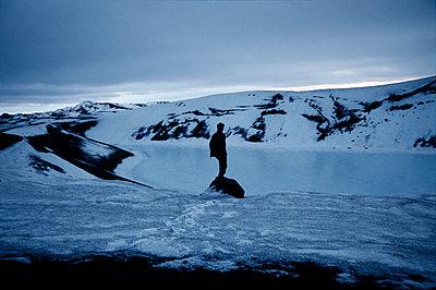 Man looking at a crater lake frozen, Iceland - p1028m2052806 von Jean Marmeisse