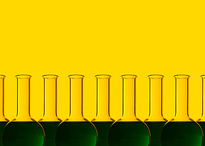 Row of test tubes with liquid, yellow background - p300m2028929 by Dreava Bogdan