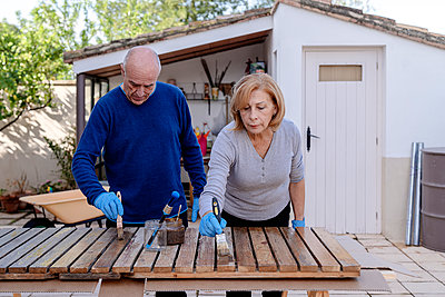 Active senior couple painting wooden plank at back yard - p300m2273579 by Albert Martínez