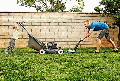 Father and son mowing lawn in backyard - p924m1081676f by Keith Berson