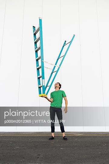 Acrobat balancing ladder upside down in his hand - p300m2012365 von VITTA GALLERY