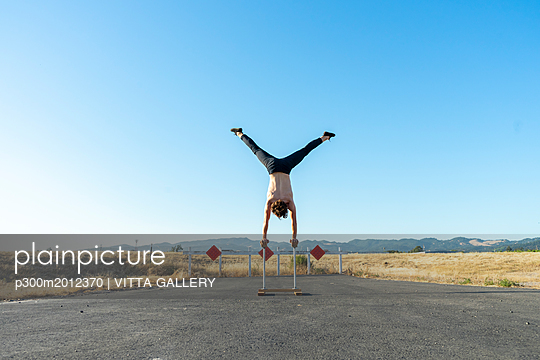 Acrobat doing handstand on handstand canes - p300m2012370 von VITTA GALLERY