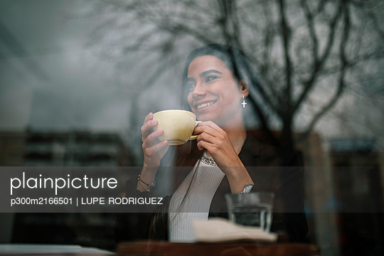 Happy young woman relaxing in a coffee shop - p300m2166501 by LUPE RODRIGUEZ