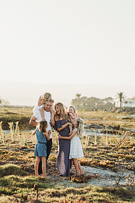 Lifestyle portrait of family with young girls smiling at beach sunset - p1166m2165891 by Cavan Images