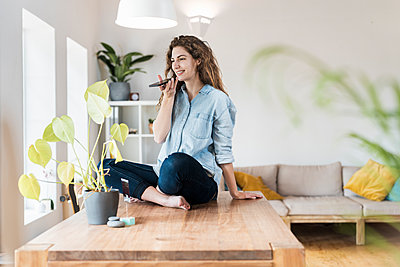 Smiling woman with crossed legs talking on mobile phone at home - p300m2276467 by Steve Brookland
