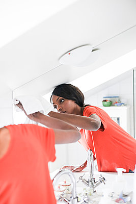Mid adult woman cleaning mirror in bathroom at home - p426m1542733 by Maskot