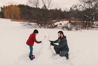 Father and daughter making snowman - p924m1230044 by Kymberlie Dozois Photography