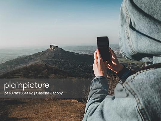Junger Mann mit Smartphone und Weitblick auf schöne Landschaft - p1497m1584142 von Sascha Jacoby