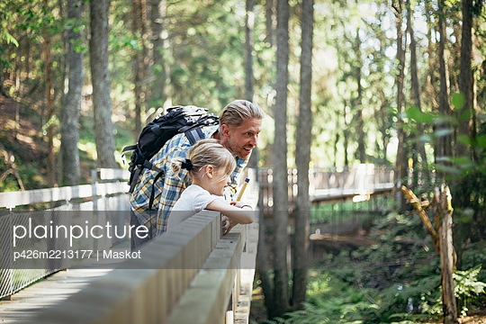 Smiling father with backpack talking to daughter on footbridge in forest - p426m2213177 by Maskot