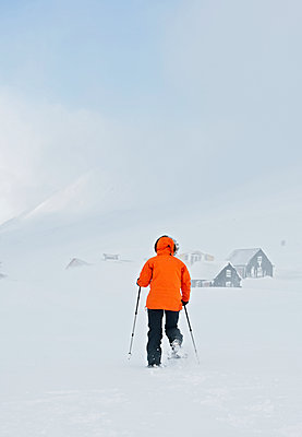 woman walking on snowshoes towards farm in Iceland - p1166m2268875 by Cavan Images