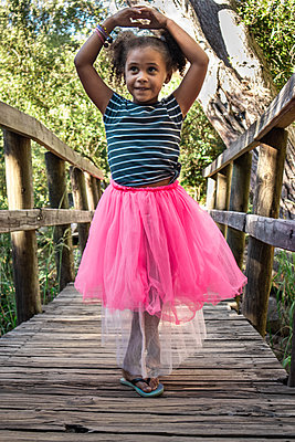 Little girl in pink tulle skirt shows a dance pose - p1640m2246829 by Holly & John