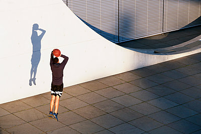 Young man playing basketball in the city - p300m1469900 by Florian Küttler