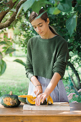 Young woman cutting pumpkin for preparing gnocchis - p300m2041599 by Alberto Bogo