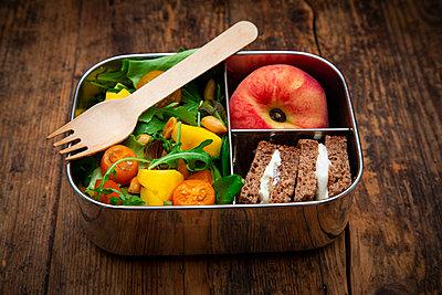 Lunchbox mit Mango-Salat (Ruccola, Spinat u.a. mit Mango und geröstetet Erdnüssen), Roggensaftbrot mit Frischkäse, Platt-Pfirsich - p300m2144363 von Larissa Veronesi